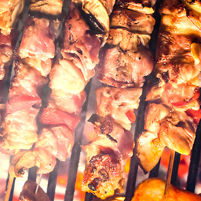 Grilling meat skewers and chicken on natural charcoal barbecue g